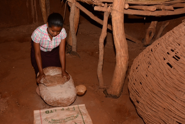 Daniel Tewa's daughter demonstrating grinding maze in original Iraqw underground house