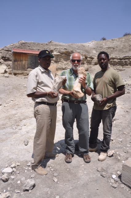 Our guide, Lucas, me and Abuu holding some monster fossils at the site where Mary Leaky found Zinjanthropus