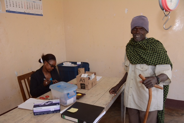 Monica, our nurse, manning the pharmacy in Upper Kitete with another satisfied customer