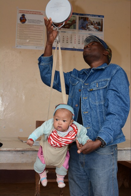 Dr. Isaac helping out with baby weights for well-baby clinic